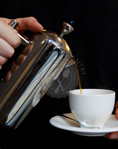 Coffee being poured in to a cup from a cafetiere
