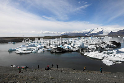 Jokulsarlon glacier lagoon with tourists and two inflatable dinghies on the shore, Austurland (Eastern Region, East Iceland),...