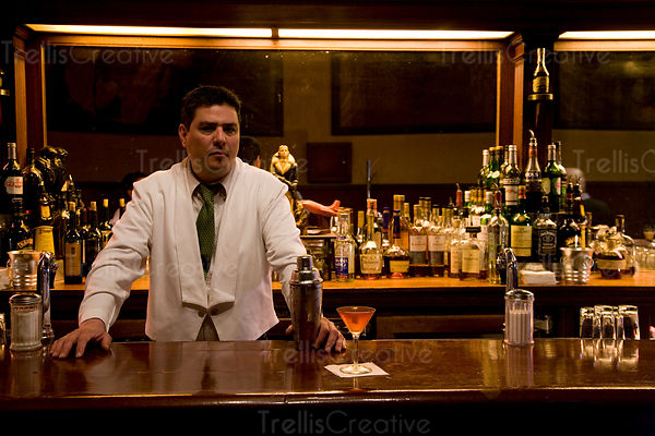 Bartender stands behind bar and poured cosmopolitian