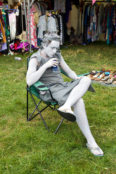 UK - Standon - A man in grey body paint drink a beer through a straw at  at the Standon Calling Festival