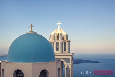 Iconic blue cupola overlooking the sea at sunset, Santorini, Greece