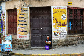 Elderly woman sitting in doorway selling items, Tarija, Bolivia