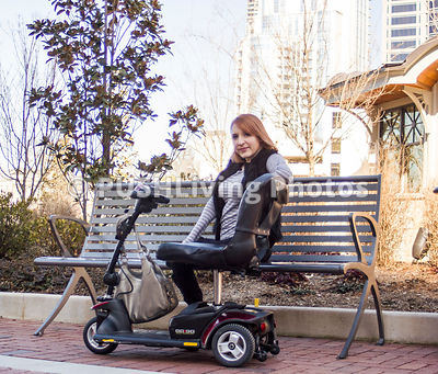 Woman sitting on  a park bench with her mobility scooter