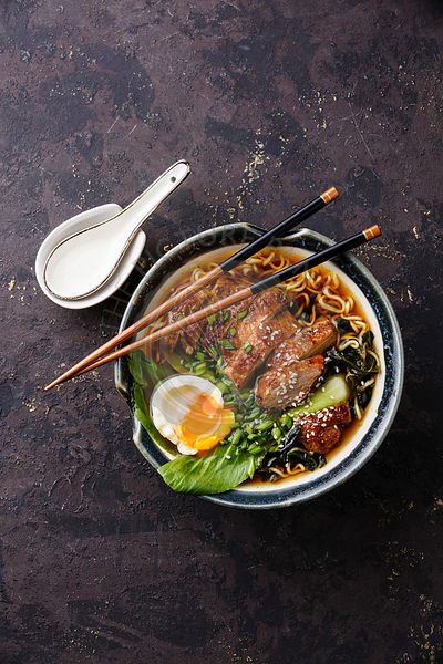 Duck noodles with egg and pak choi cabbage in bowl on dark black stone texture background