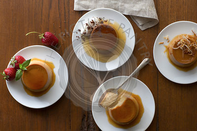 Assorted flavored individually plated flans photographed on a rustic wood surface with vintage silverware and linens.