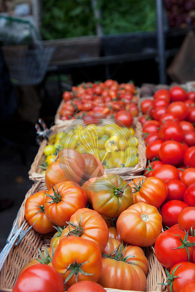 Mixed tomatoes in baskets on market stall