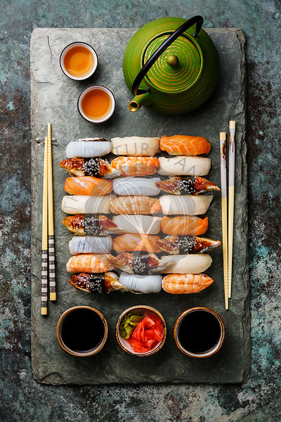 Nigiri sushi set for two on gray stone slate plate board and green tea