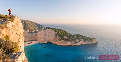Panoramic of woman on cliff edge over shipwreck beach. Zakynthos, Greece