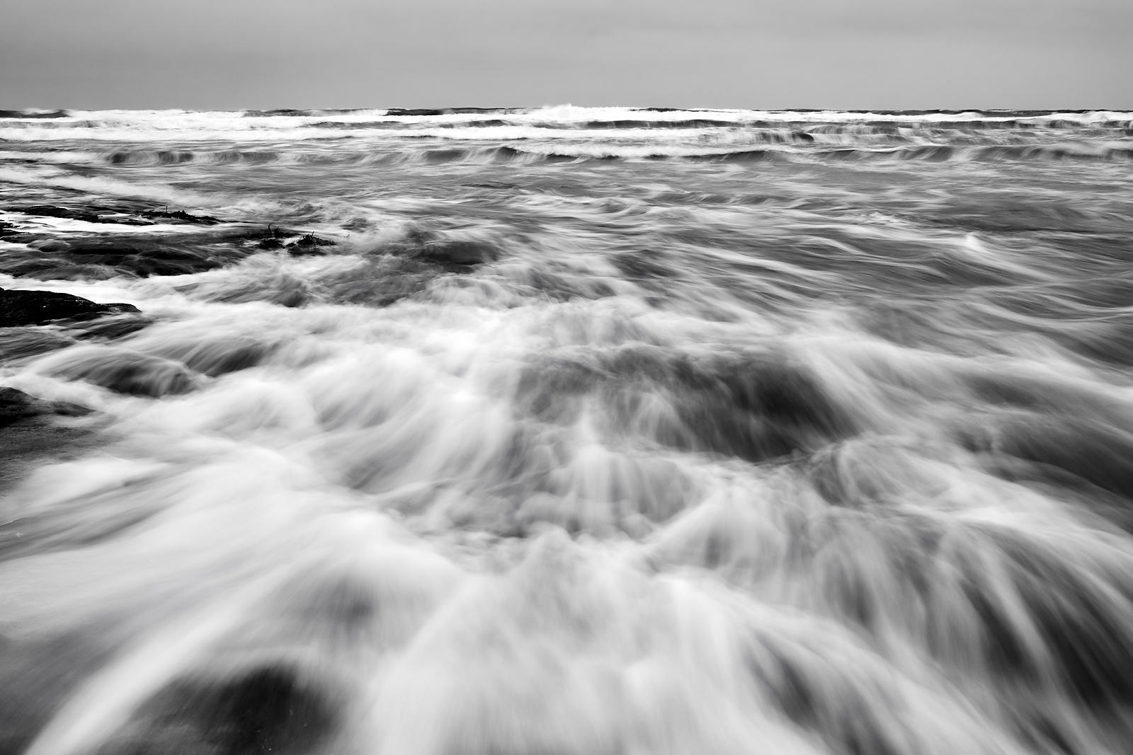 Soft waves over the rocks in black and white