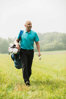 Golf player walking on a meadow