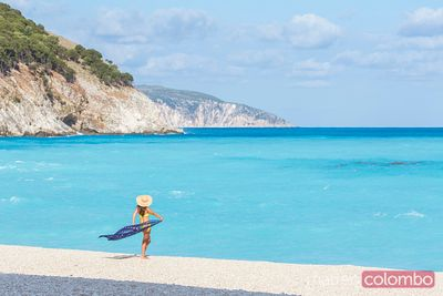 Woman with sarong on Myrtos beach. Kefalonia, Greek Islands, Greece
