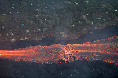 Aerial view of lava river, flowing past remaining homes, toward Kapoho, Puna District. Lava emanating from  erupting from fis...