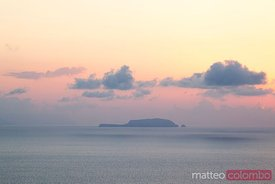 DIstant island at sunrise in the aegean sea Santorini Greece