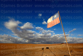 Chilean national flag and dramatic clouds over the Atacama Desert near Pica, Region I, Chile