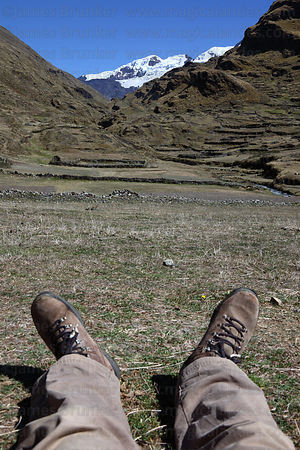 Hiker taking a break in valley below snowy peaks, Cordillera Apolobamba , Bolivia