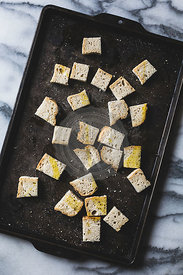 Croutons - crusty bread cubes covered in olive oil, about to be toasted.