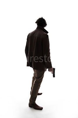 A silhouette of a standing man, holding a gun, in a leather Jacket – shot from eye level.