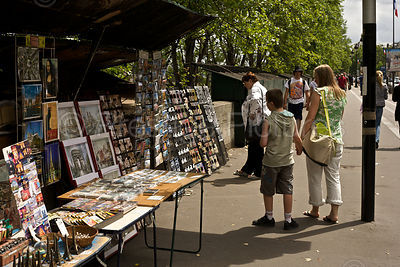 Tourists Look at Postcards for sale by the River Seine