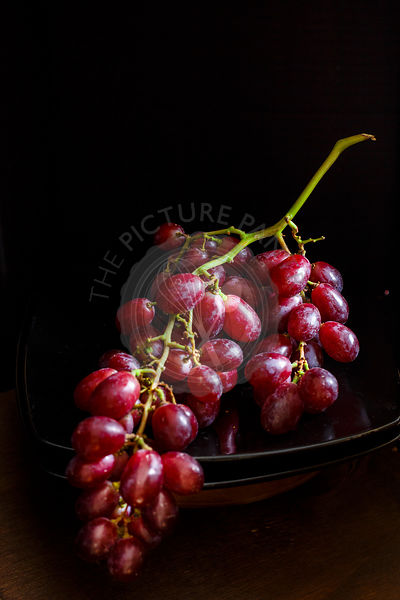 Fresh bunch of red grapes on a dark background.