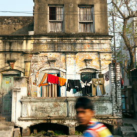 A boy cycles past old French colonial houses on the streets of Chandannagar