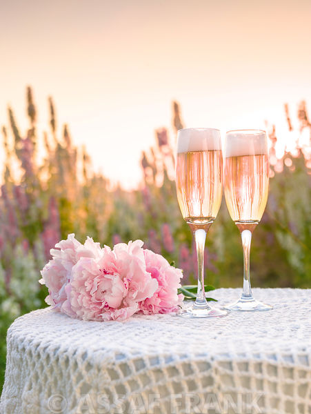 Champagne glasses and Peony flowers on a table in a field at sunset
