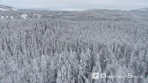 Flying above snowy forest toward railroad trestle in Alaska