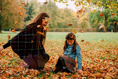 Young woman and little girl playing with autumn leaves on a meadow