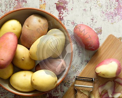 Washed red and white potatoes in a bowl and one with the skin partially peeled.