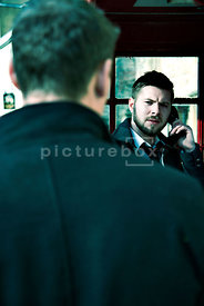 An atmospheric image of a man from behind, looking at another man in an English telephone box.