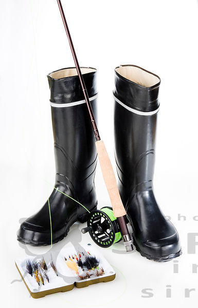 Rubber boots with fly fishing equipment