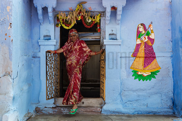 Woman in a Red Sari and Green Chappals Stepping out of her House