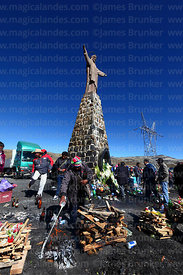 Aymara shaman or yatiri pours beer in a circle around offerings (called k'oas) to Pachamama below Christ statue, La Cumbre, C...