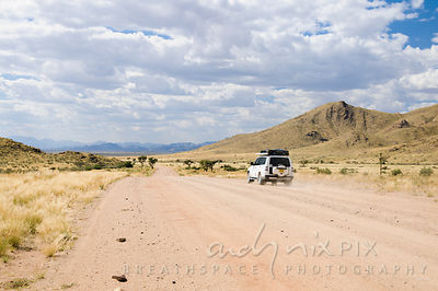 A single luxury 4x4 vehicle driving on a flat dirt raod through the desert, mountains in the distance.