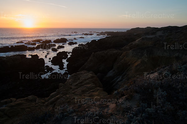 Rocky shore line with the water creeping in at sunset