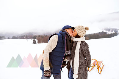 Kissing senior couple with sledge in snow-covered landscape