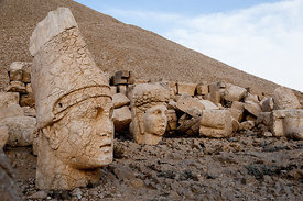 The west terrace of Mount Nemrut with heads of the colossal statues and the tumulus.  Head of Antiochos I in foreground with ...