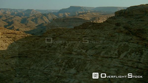 Aerial shot side of weathered rock formation and at gap wide angle of mountain ranges with partial river and desert sand belo...