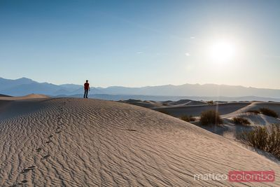 Man admiring sunrise over sand dunes, Death valley , USA