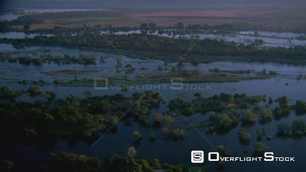 Aerial wide angle shot small groups of trees and land spits in river at sunset sunrise Zimbabwe