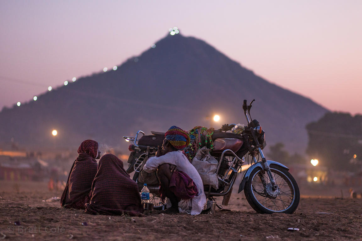 People chat next to a motorcycle at the Pushkar Camel Mela, Pushkar, India.