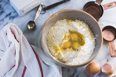 A mixing bowl with eggs and flour, ready for baking.