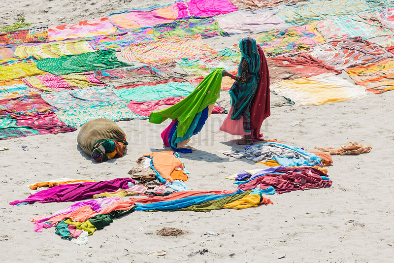 Woman Collecting Saris after Drying on a Sand Bar in the Yamuna River