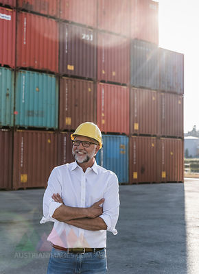 Businessman at cargo harbour, wearing safety helmet, arms crossed