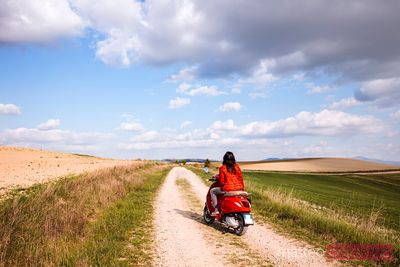 Tourists riding a scooter on a country road in Tuscany