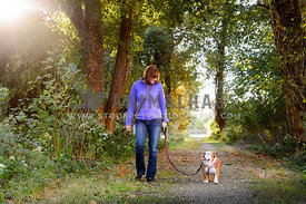 person and dog walking down path looking at eachother