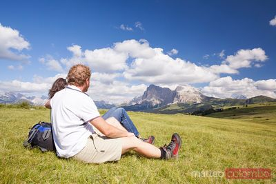 Couple relaxing on meadow in the mountains