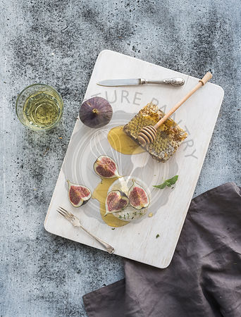 Camembert cheese with fresh figs, honeycomb and glass of white wine on serving board over grunge rustic grey backdrop