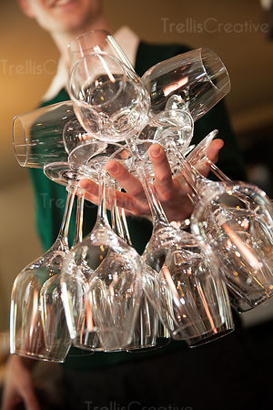 A person balancing empty wine glasses in one hand
