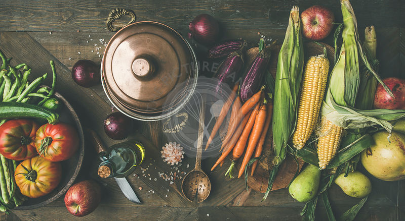 Flat-lay of green beans, corn cobs, carrot, tomatoes, eggplant, pears, apples over rustic wooden table