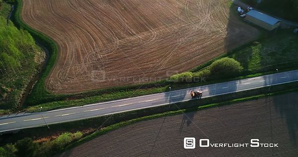 Tractor on the Road, Aerial View Following a Fertilizer Machine Leaving the Field and Driving on a Asphalt Route, on a Sunny ...
